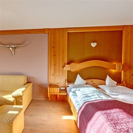 Double bed with purple bedspread and couch from the Alpine Feel Good Suite Innsbruck