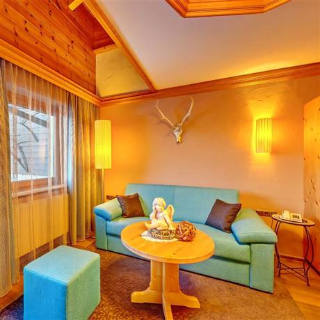 Green-blue couch in the living area of the Family Suite Kitzbühel