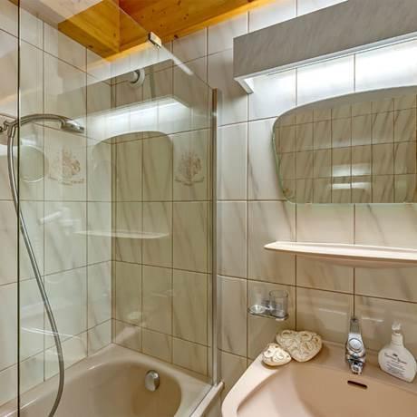 Blick auf Dusche, Badewanne und Waschbecken im Badezimmer von der Familiensuite Kitzbühel