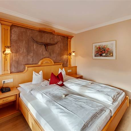 Double bed and picture with roses in the Comfort Double Room Seeblick