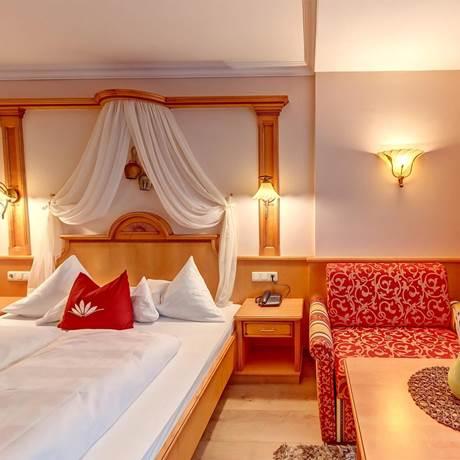 Großraumblick auf Doppelbett und rotem Sessel beim Komfort-Doppelzimmer Waldruhe
