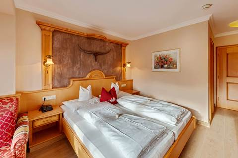 Doppeltbett und Bild mit Rosen im Komfort-Doppelzimmer Seeblick