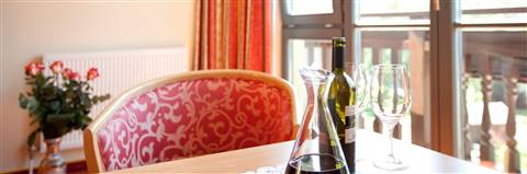 Chair and table with wine bottle in the Comfort Single Room Seeblick