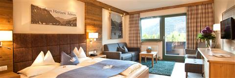 Double bed with blue bedspread and chequered couch in the Comfort Double Room Kaiserblick zum See