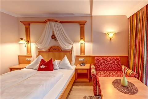 Large view of the double bed and red armchair in the Comfort Double Room Waldruhe
