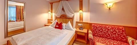 Blick auf Doppelbett und Sessel im Komfort-Doppelzimmer Waldruhe