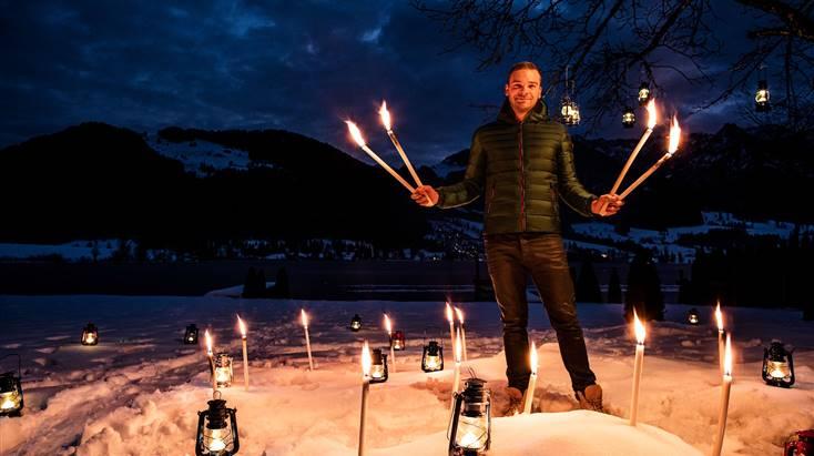 Mann steht mit Feuerfackeln am Strand bei Nacht