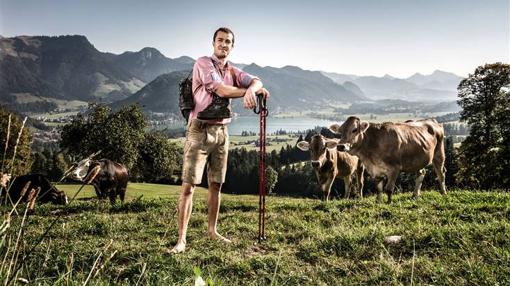 Man in traditional dress standing on an alpine meadow