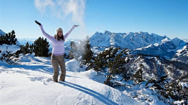 Frau in Winterkleidung wirft Schnee in die Luft
