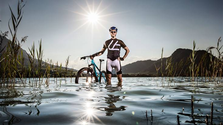 Man stands with mountain bike in the lake Walchsee