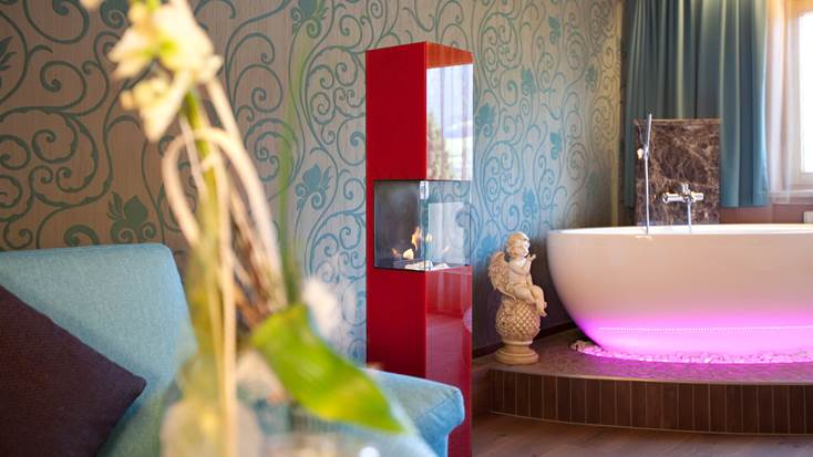 Decorative fireplace and bathtub in the Private Wellness Suite Tirol