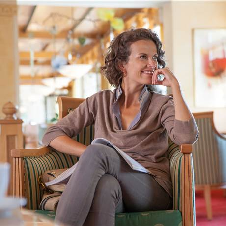Woman sitting on a chair in a hotel lobby smiling