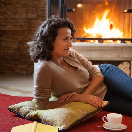 Woman lying in front of a fireplace with a cup of coffee