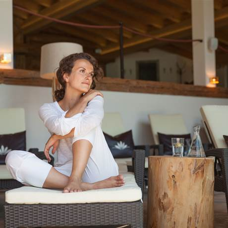 Woman sits on a couch and looks thoughtfully