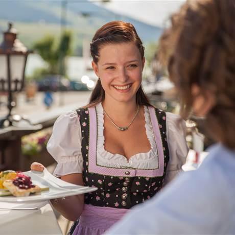 Frau in Tracht serviert Speise auf einem Teller