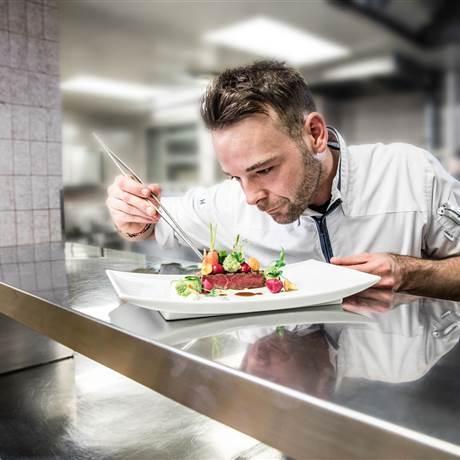 Koch richtet Teller auf Küchenpass an