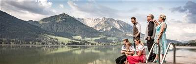 Family stands on a jetty directly at the lake in front of mountain scenery