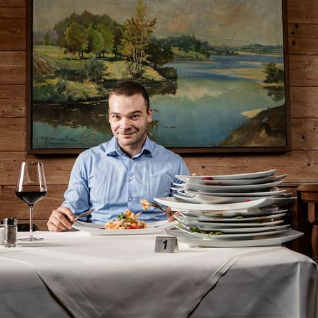 Man sits in front of stacked plates in a restaurant
