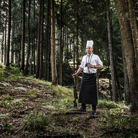 Man in chef's hat standing in the forest with a hunting rifle