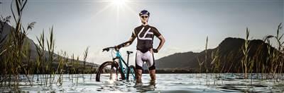 Mountainbiker steht mit Rad im See