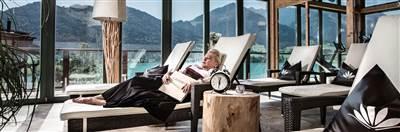 Frau entspannt auf einer Liege vor einer Panorama-Glaswand
