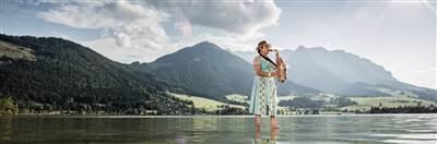 Woman standing on a lake playing saxophone