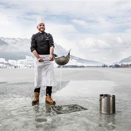 Man ice-fishing on a frozen lake