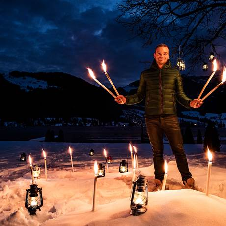 Man stands with torches in the snow