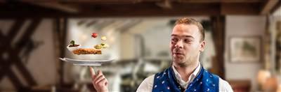 Mann hält Teller in der Hand mit schwebenden Gerichten