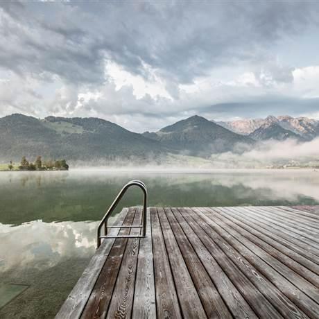 See vor Bergkulisse und Nebelschwaden