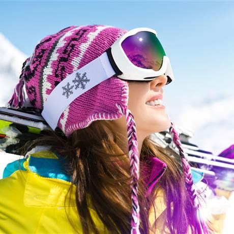 Skifahrerin mit Skibrille schaut in die Sonne