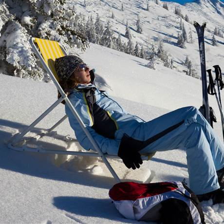 Woman in ski outfit takes a rest in the snow and relaxes on a folding chair
