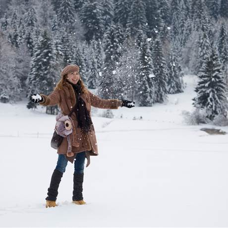Woman stands on a snow-covered field and throws snow into the air
