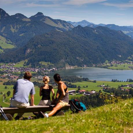Family sits on a mountain meadow and looks towards the valley at a lake