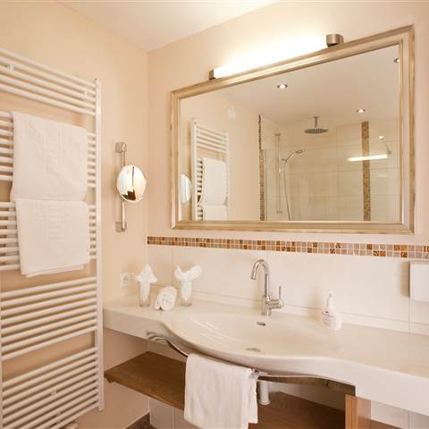 Large bathroom with bath radiator and towels