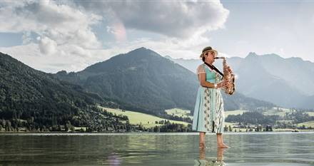 Woman standing on a lake playing saxophone