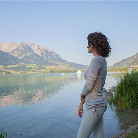 Woman stands at the lake in front of a mountain scenery