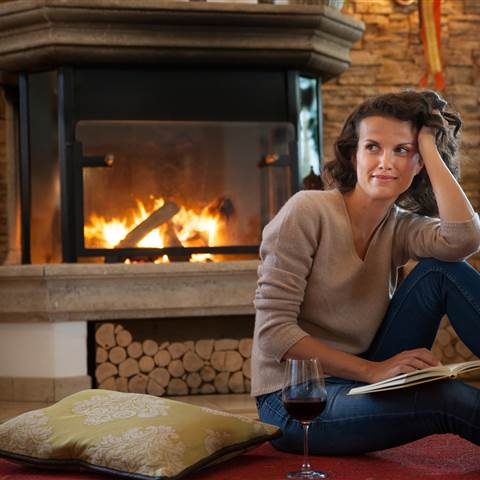 Woman sitting in front of a fireplace with a book and a glass of red wine