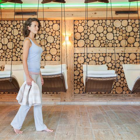Woman with dark hair stands in front of wellness loungers