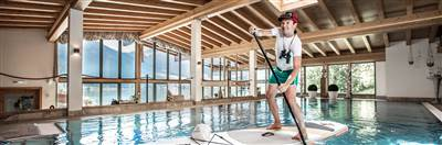 Man doing SUP in a panorama indoor swimming pool
